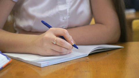 Student dressed in a white chemise sits at a school desk writing text in exercise book using ballpoint pen. Close-up