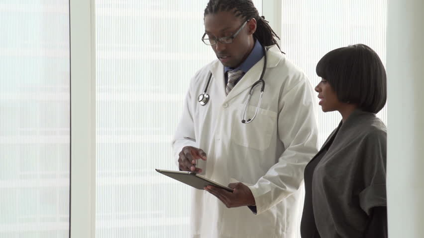 Doctor walking with patient with tablet, close up
