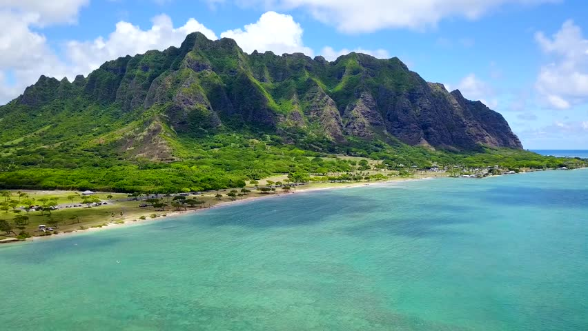 Aerial Scenic flyover footage of ocean of Chinamans Hat, Oahu Hawaii.  Tropical view of Kualoa Valley, Koolau Mountain. Kaneohe Bay side. Turquoise-blue water lovely with blue sky. 4K UHD drone shot. | Shutterstock HD Video #30760309