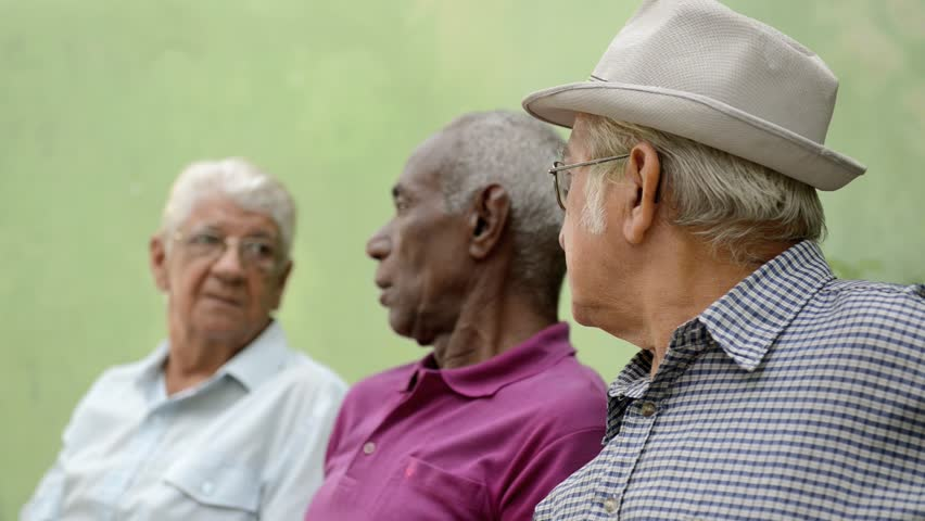 Active retirement and senior people, group of three old male friends talking and laughing on bench in public park. Sequence