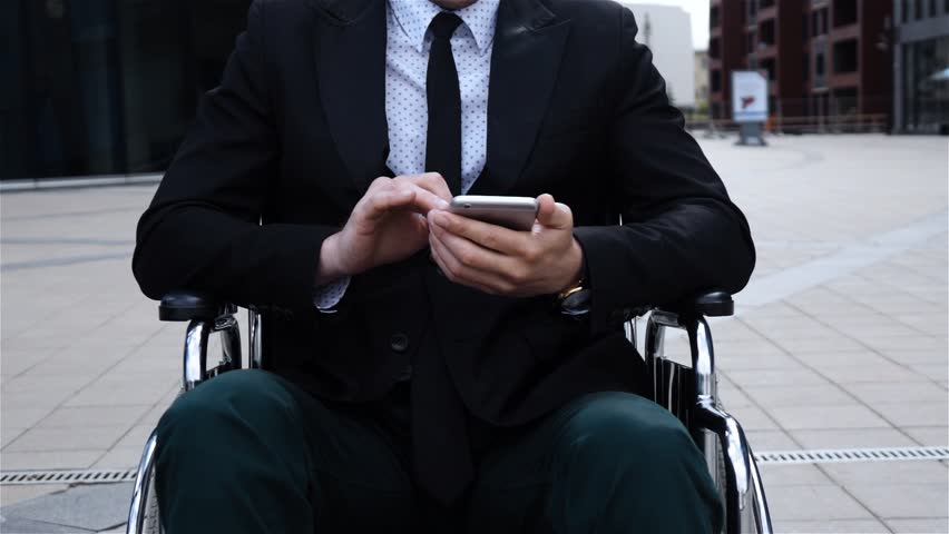 Male entrepreneur  working with mobile phone, physically disabled man sits in wheelchair at businesscentre district, disabled self-confidence, super slow motion shot. | Shutterstock HD Video #30794539