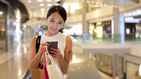 Woman using mobile phone and shopping bags