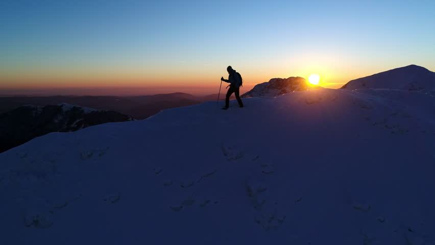 Aerial - Epic tracking shot of male mountaineer walking on snowy mountain ridge at colorful sunset in winter | Shutterstock HD Video #30811780