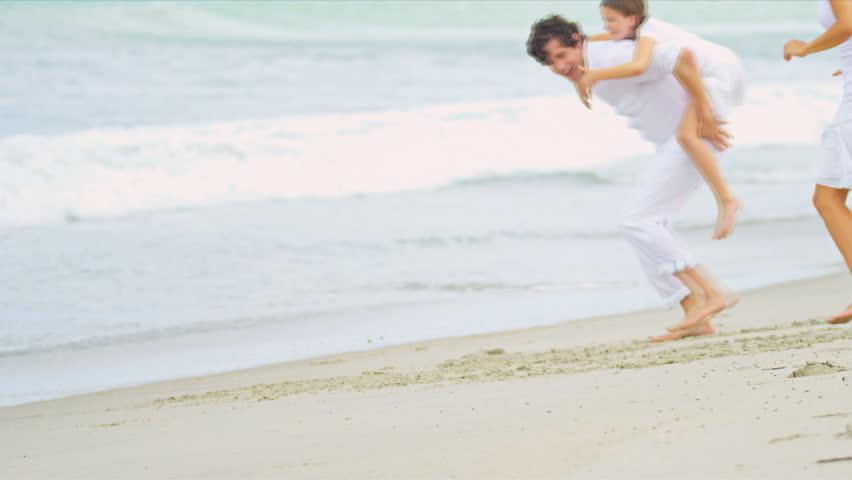 Caucasian happy parents having fun together daughter piggyback on beach