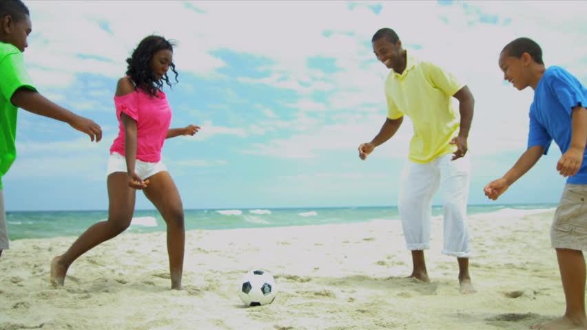 African American children enjoying summer kicking football with father on beach