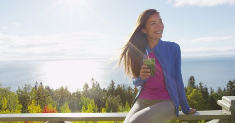 Healthy eating girl drinking green smoothie detox outdoors in fall autumn foliage nature retreat. Happy woman on weight loss diet vegan nutrition cleanse.