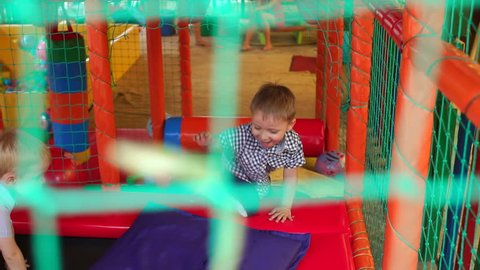 Three small happy children jumping on a trampoline on the bright plastic soft Playground in the entertainment center, in the foreground blurred green mesh.