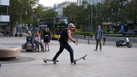 BERLIN, GERMANY - SEP 10, 2017: Aged strong man shows skateboard riding performance tricks entertaining tourists on center street square