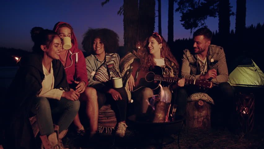 Happy Young Group Of Campers Sitting Around Bonfire In Forest Singing Along To Guitar Drinking And Laughing Music As Lifestyle Musical Leisure Concept Slow Motion Shot On Red Epic W 8k #30848359
