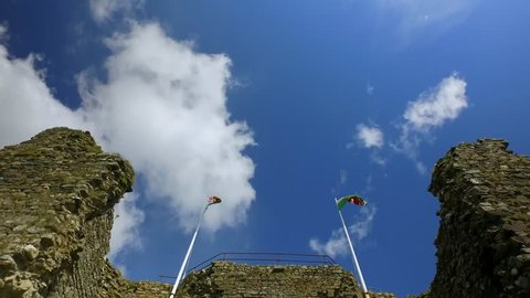 Two Welsh flags blowing in the wind on top of an old stone wall.