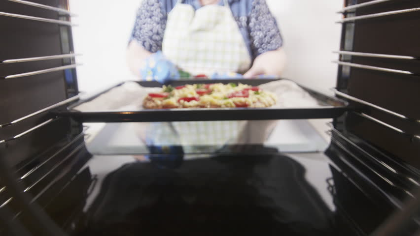 View from inside of the oven. Cooking italian pizza in electric convection oven. Woman placing pizza on a baking sheet inside hot cooker. Frozen pizza topped with salami tomatoes mozzarella cheese.