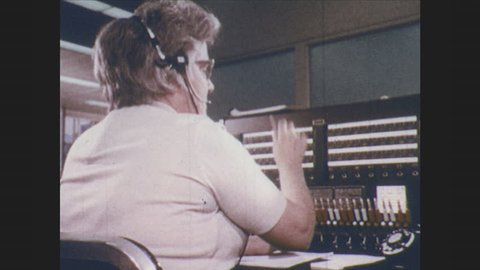 1970s: Switchboard operator. Maintenance men. Factory workers. Clerk. Car salesman. Movie theater ticket booth. Train driver. Astronaut. Politician. Welder. Job chart. Men talk on phone.