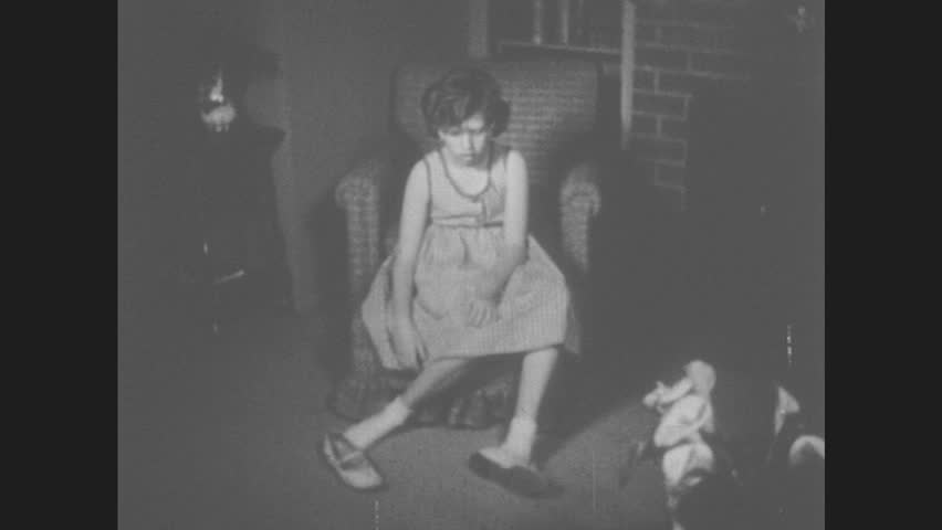 1950s: Girl sits in chair imagining clown feet. Woman hands girl black shoes. Girl's foot in black shoe. Girl dances around living room in black shoes. Girl shoes black shoes to man and spins around.   Shutterstock HD Video #30957139