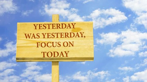 Yesterday was yesterday focus on today. Words on a wooden sign against time lapse clouds in the blue sky.