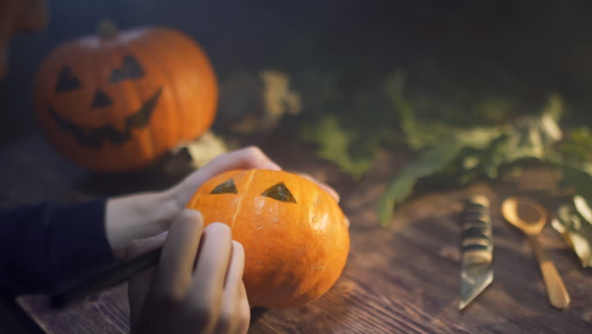 young womanDrawing eyes and mouth on Halloween pumpkin to carve a Jack 'o' Lantern on wooden table with candles. The winter squash embodies the spirit of autumn like: Halloween,Thanksgiving, harvest