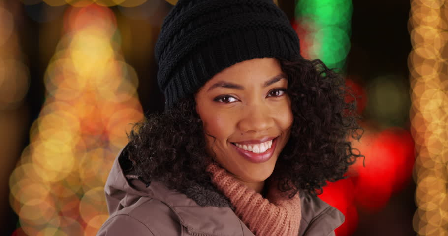 Close up of cute African American female smiling joyfully at camera, festive bokeh lights in background. Portrait of black woman in winter coat in outdoor setting at night, smiling. 4k | Shutterstock HD Video #31014829