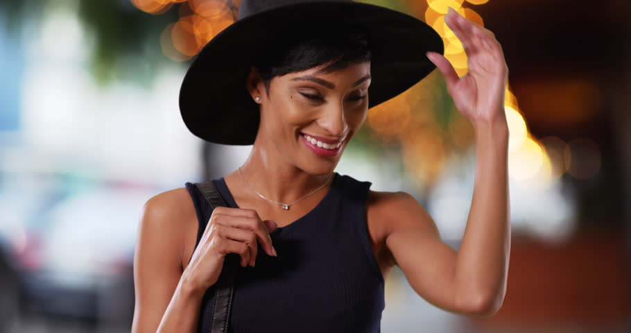Classy African American female modeling stylish black hat on urban street 5f3c2c26f6b