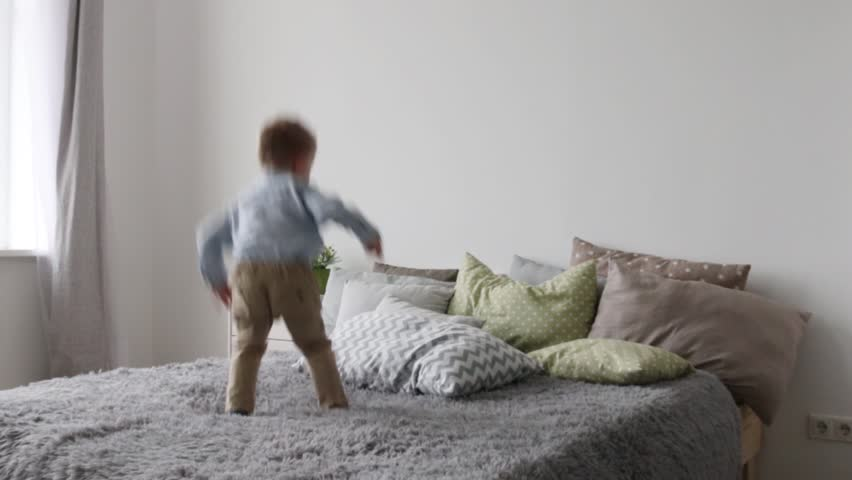 Little happy boy jumps on bed with pillows in bedroom  #31027105