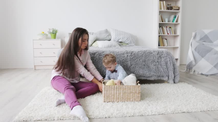 Little happy boy and his mother play with toys in bedroom  #31027138