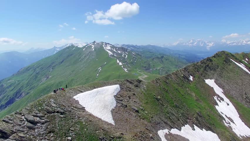 Flying around group of hikers tourists over mountain range Aerial 4k video. Hiking Travel Tourism Caucasus Svaneti, Georgia.