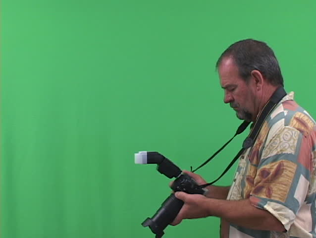 Photographer with camera shooting with flash, shot on a greenscreen