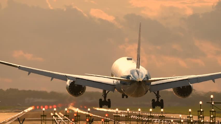 Passenger airplane landing towards the runway during sunset.