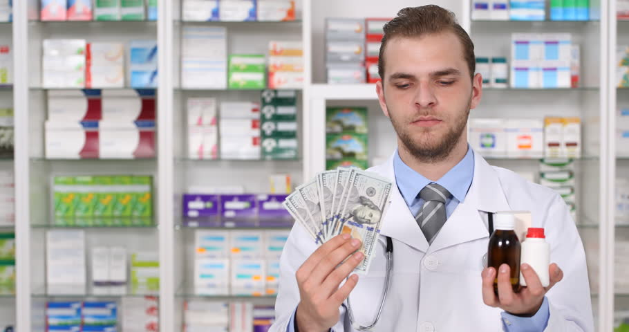 Pharmacist Man Show Us Dollars and Drugs Medicine Expensive Treatment Pharmacy