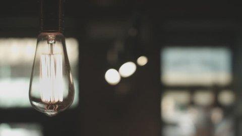 Vintage lighting decoration. Classic edison lamp. Hanging light bulb. Close up of an incandescent lamp. Vintage lamp light on. Edison lightbulb in the dark