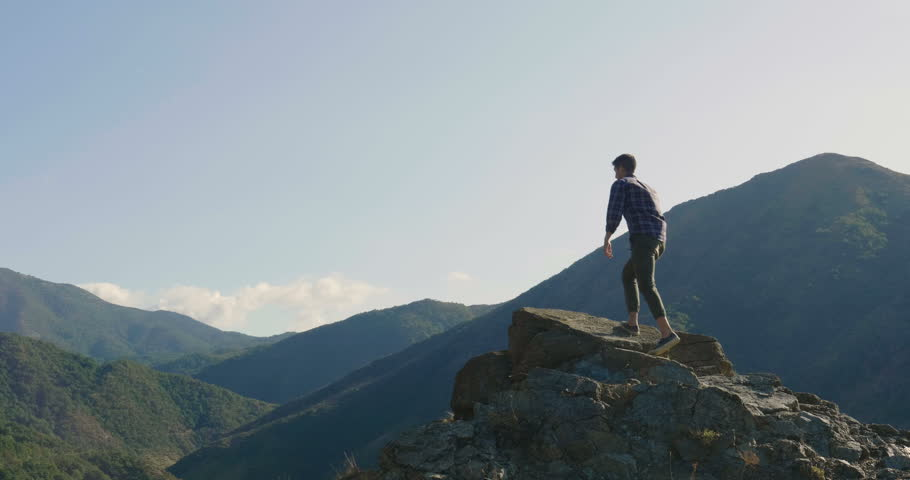 On the edge of a rocky cliff a man raises his hands to heaven as a sign of freedom or victory and in the background a fantastic landscape. Concept of: breathing, freedom, journey, life, love. | Shutterstock HD Video #31081786