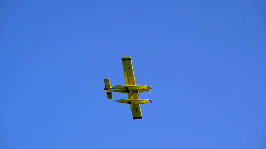 Fire fighter airplane flying over towards forest fire on the other side of the bay. Shot in slow-motion hd