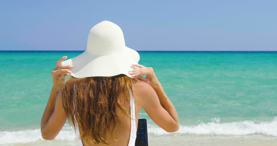 A beautiful woman on holiday with the white costume and the straw hat on the shore of a beautiful sea uses the computer to work or shop. Concept of: vacation, work, shopping,... | Shutterstock HD Video #31087924
