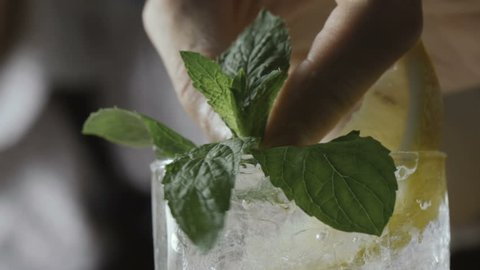 Barman decorates a cold cocktail with herbs