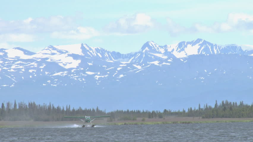 A pretty, green DeHavilland Beaver floatplane takes off from Beluga Lake in Homer, Alaska. The Kenai Mountains loom beyond.