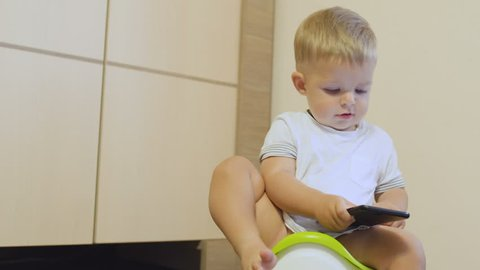 Cute little boy plays with phone sitting on the potty