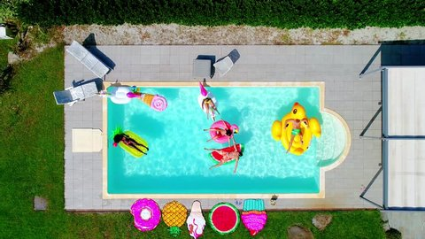 Group of friends having fun on the air mattress in the swimming pool. Different inflatable beds of various colors and shapes