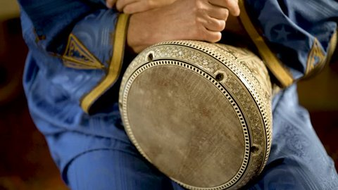 Tight shot of man in Moroccan dress playing arabic doumbek, darbuka