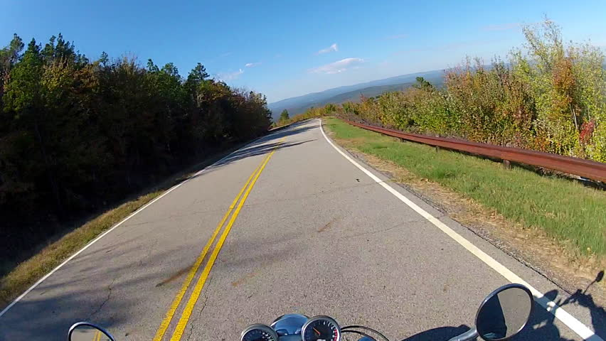 A helmet cam point of view shot of a motorcycle speeding down a forested