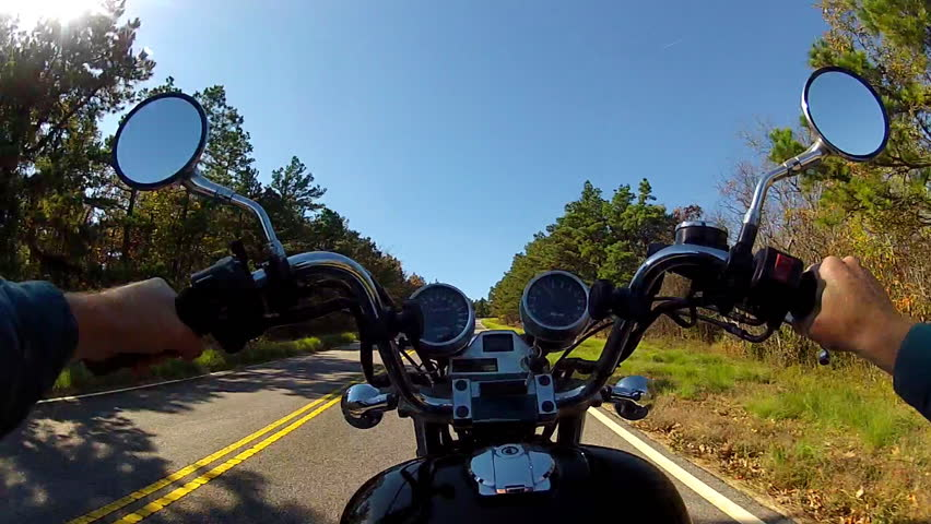 A wide angle point of view shot of a motorcycle climbing a steep and forested