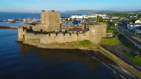 Medieval Norman Castle in Carrickfergus near Belfast, Northern Ireland,  in sunrise light. Aerial flyby video with marina, yachts, parking, town and far view of Belfast in the background