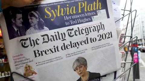 """PARIS, FRANCE - SEP 23, 2017: Man buying latest The Daily Telegraph newspaper from press kiosk with Braking news from Theresa May British Prime Minister """"Brexit delayed to 2021"""""""