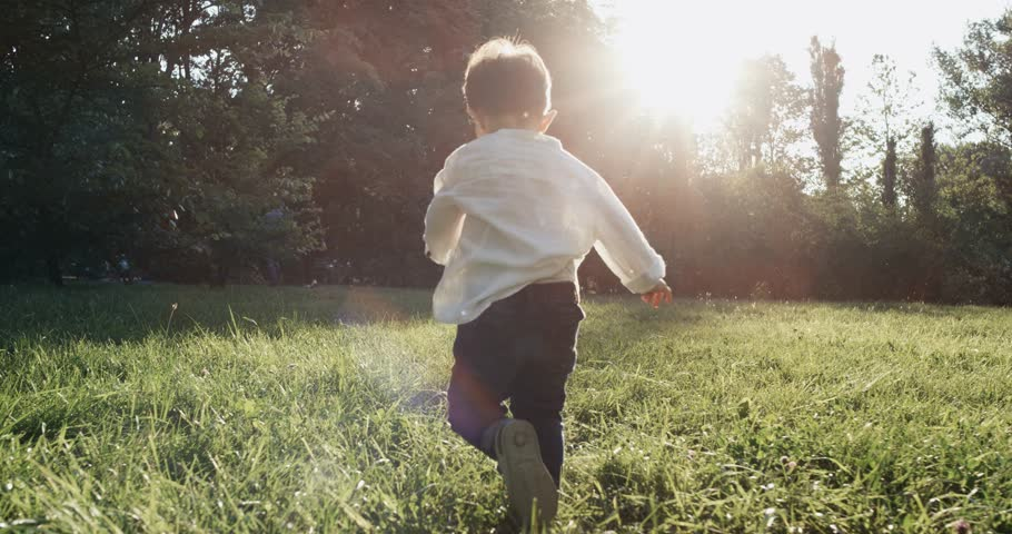Little boy Running outside. Ultra slow motion of child running at outside home garden. The child runs to the sunset. 4k