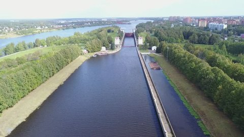 4K high quality aerial drone video of Moscow river channel connecting it to Russia's great river Volga, gateways, waterways with vessels near town Dmitrov 70 km north of Moscow, Russia on summer day