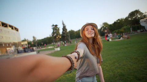 caucasian happy red-haired girl walking in park holding man by hand making follow me story in slow motion