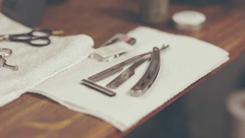 Barber shaving accessories. Barber shave razor. Barber preparing straight razor for shaving client in barbershop. Barber tools on white napkin