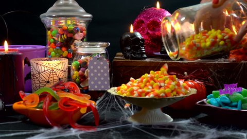 4k Happy Halloween trick or treat party table with bowls and apothecary jars of candy with skull candles against a black background, setting up table time lapse.