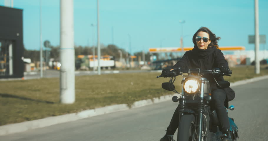 TRACKING Beautiful Caucasian female biker riding her motorcycle near warehouse. 4K UHD RAW edited footage