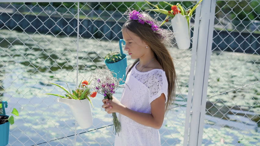 Gentle little girl with flowers in hand smiling and looking at camera on bay bar
