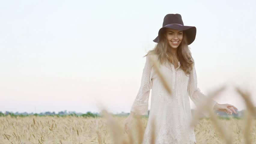 Happy young pretty woman in white dress and black hat running in the field
