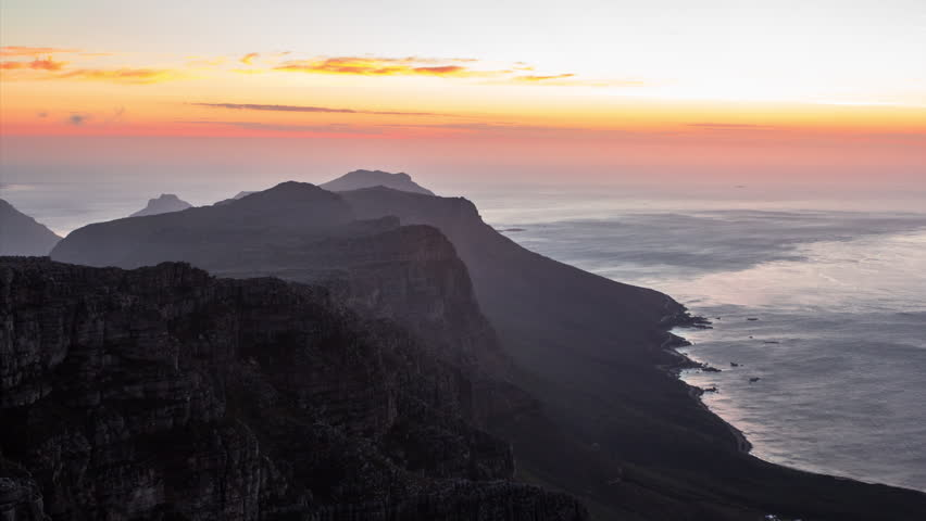 A static time lapse of the sun setting from the top of Table Mountain in Cape Town, South Africa. Views of the ocean and the Twelve Apostles peaks with Camps bay below and vivid sun set colors.