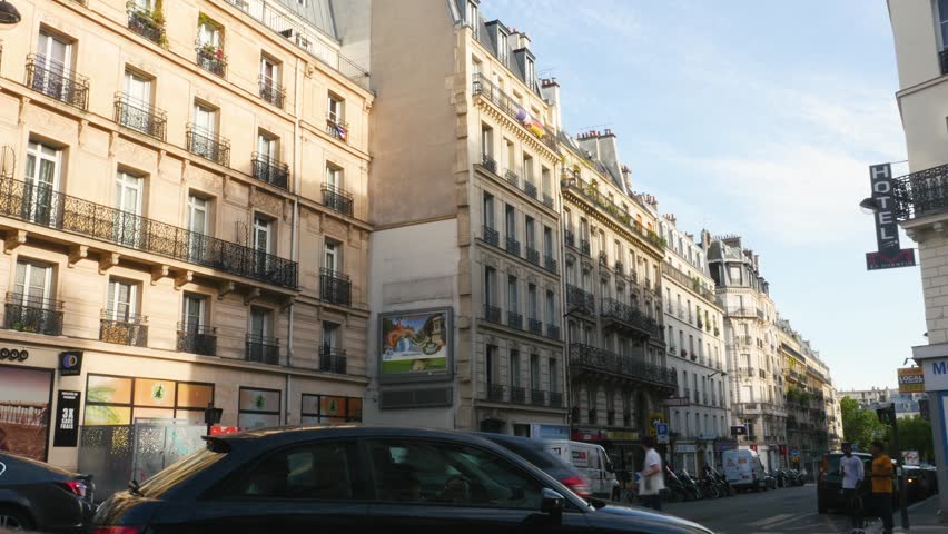 Paris, France - Circa 2017: Rue de Saint-Quentin in Paris with majestic French Architecture and apartment buildings, hotels, cars, pedestrians on a warm summer day
